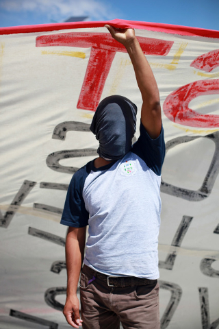 A masked student holds a banner as he participates, with hundreds of other students and relatives of missing students, in blocking a main highway in the city of Chilpancingo, Mexico, Sunday Oct. 5 ...