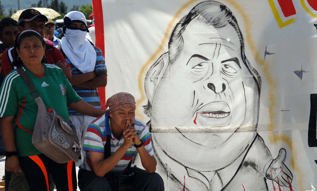 Students and the relatives of missing students stand next to a banner showing a cartoon of Guerrero state Governor Angel Aguirre as they block a main highway in Chilpancingo, Mexico, Sunday, Oct.  ...