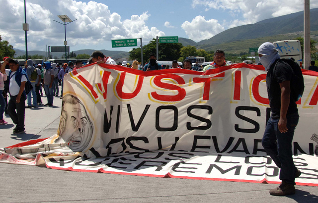 Students and the relatives of missing students unfurl a banner as they block a main highway in Chilpancingo, Mexico, Sunday, Oct. 5, 2014. Protesters are demanding answers a day after security for ...