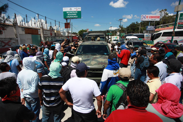 Students and relatives of missing students surround and deny access to a convoy of military vehicles as they block a main highway in the city of Chilpancingo, Mexico, Sunday Oct. 5, 2014. Students ...