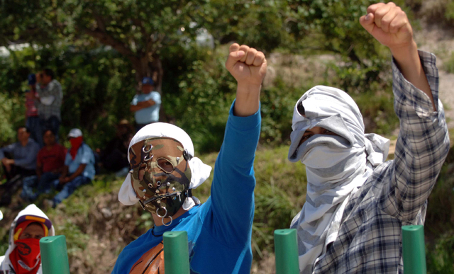 Masked students raise their fists as they block a main highway in Chilpancingo, Mexico, Sunday, Oct. 5, 2014. Students and relatives are demanding answers a day after security forces investigating ...