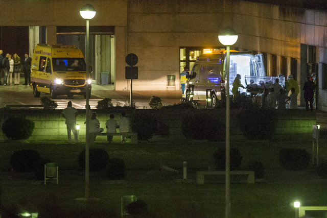 Medical personnel carry a Spanish nurse who believed to have contracted the ebola virus from a 69-year-old Spanish priest into the ambulance before they leave Alcorcon Hospital in Madrid, Spain, T ...