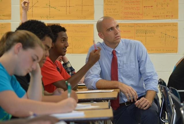 In this May 27, 2014 photo provided by the Jacksonville Public Education Fund, Brian Ellis, an algebra teacher, works with his students at First Coast High School. A Monday, Oct. 6, 2014 report by ...