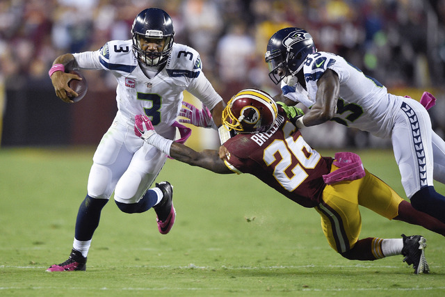 Seattle Seahawks quarterback Russell Wilson (3) escapes the grasp of Washington Redskins strong safety Bashaud Breeland (26) during the first half of an NFL football game in Landover, Md., Monday, ...