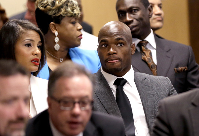 Minnesota Vikings running back Adrian Peterson, right, sits with his wife Ashley Brown Peterson, left, during his first court appearance Wednesday, Oct. 8, 2014, in Conroe, Texas A Texas judge has ...