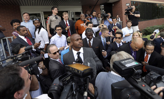 Minnesota Vikings running back Adrian Peterson, center, navigates through members of the media after making his first court appearance Wednesday, Oct. 8, 2014, in Conroe, Texas. A Texas judge has  ...