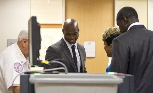 Minnesota Vikings running back Adrian Peterson goes through security at the Lee G. Alworth Building as he arrives for court in Conroe, Texas Wednesday, Oct. 8, 2014. Peterson arrived to face a cha ...