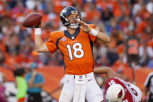 In this Oct. 5, 2014, file photo, Denver Broncos quarterback Peyton Manning (18) throws against the Arizona Cardinals during the second half of an NFL football game, in Denver. The Broncos won 41- ...