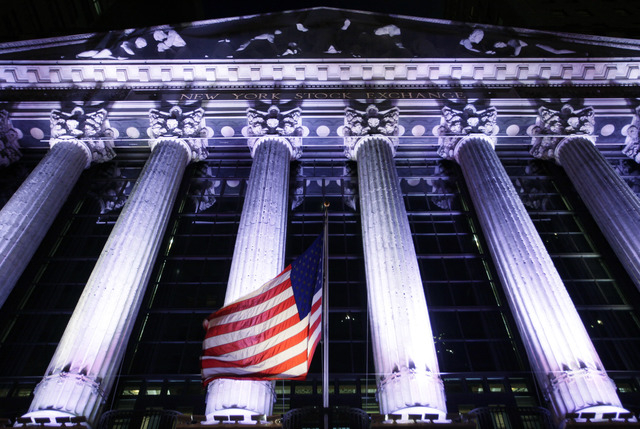 An American flag flies in front of the New York Stock Exchange, Wednesday, Oct. 8, 2014 in New York. Stocks are moving between gains and losses in early trading as traders digest the latest corpor ...