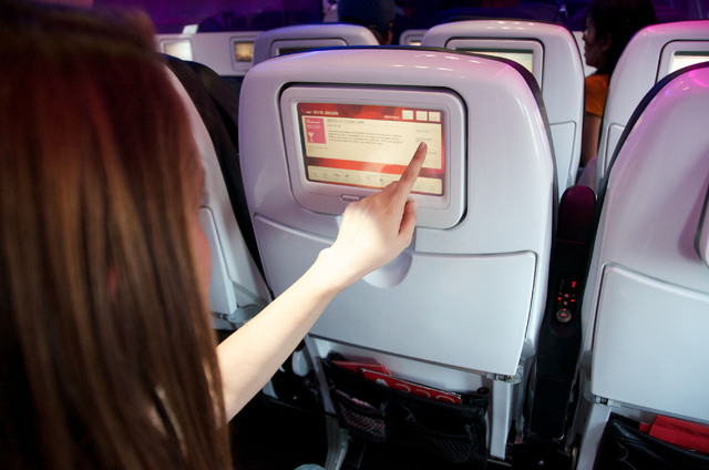 In this April 22, 2013 file photo provided by Virgin America, the airline's seat-to-seat cocktail delivery service is demonstrated aboard a Virgin America aircraft, in San Francisco. Passengers ch ...