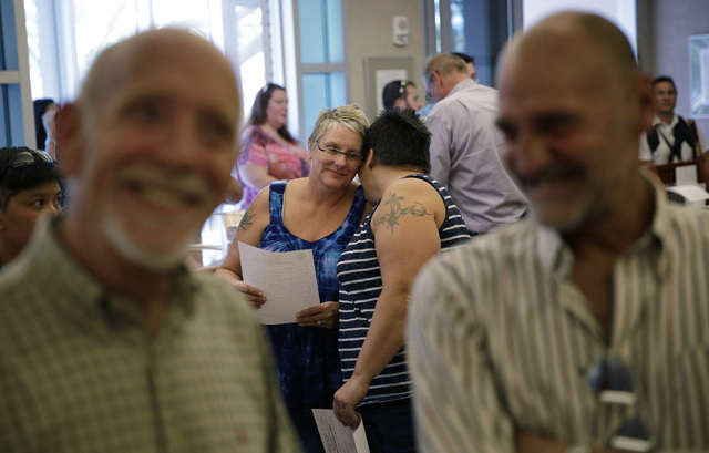 Tara Traynor, center right, embraces her partner Cathy Grimes while waiting in line for a same sex marriage license at the Marriage License Bureau, Wednesday, Oct. 8, 2014, in Las Vegas. The coupl ...