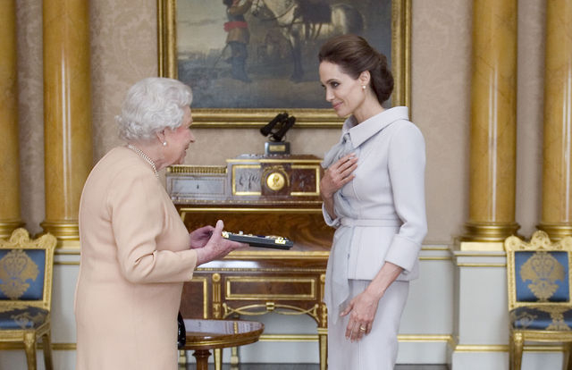 U.S actress Angelina Jolie, right, is presented with the Insignia of an Honorary Dame Grand Cross of the Most Distinguished Order of St Michael and St George by Britain's Queen Elizabeth II at Buc ...