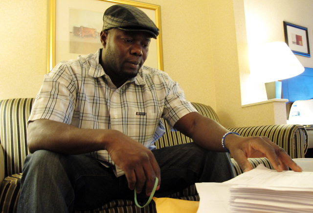 Josephus Weeks, nephew of ebola patient Thomas Eric Duncan who died earlier this week in Dallas, looks through hundreds of pages of medical documents in a hotel room Friday, Oct. 10, 2014, in Kann ...
