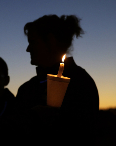 A person holds a candle as they join others at an anti-bullying rally Sunday, Oct. 12, 2014, in Sayreville, N.J.The central New Jersey town has been rocked by allegations of hazing on its football ...