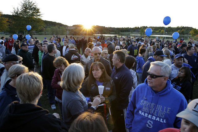 Hundreds of people gather in the setting sun, for an anti-bullying rally unday, Oct. 12, 2014, in Sayreville, N.J.The central New Jersey town thas been rocked by allegations of hazing on its footb ...
