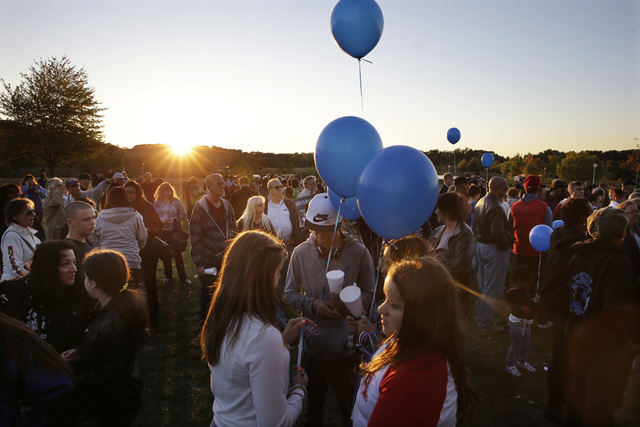 Hundreds of people gather in the setting sun, for an anti-bullying rally Sunday, Oct. 12, 2014, in Sayreville, N.J. The central New Jersey town that's been rocked by allegations of hazing on its f ...