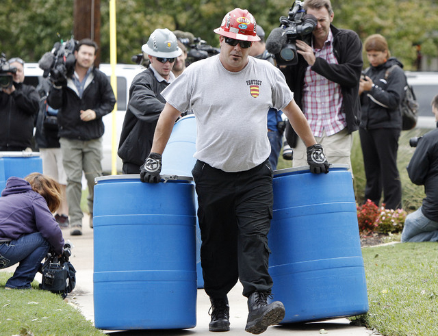 Protect Environmental workers move disposal barrels to a staging area outside the apartment of a healthcare worker who treated Ebola patient Thomas Eric Duncan and tested positive for the disease, ...
