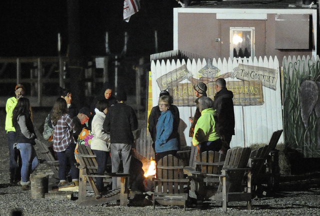 People gather around a fire at Harvest Hill Farms after a hayride accident that injured multiple people Saturday, Oct. 11, 2014, in in Mechanic Falls, Maine.  Police in Maine confirm a teen has di ...