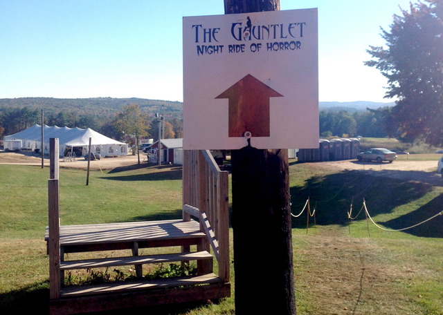 A sign attached to a pole points in the direction of the Gauntlet Haunted Night Ride at Harvest Hills Farm, in Mechanic Falls, Maine, Sunday, Oct. 12, 2014. The farm was closed after a Halloween-t ...