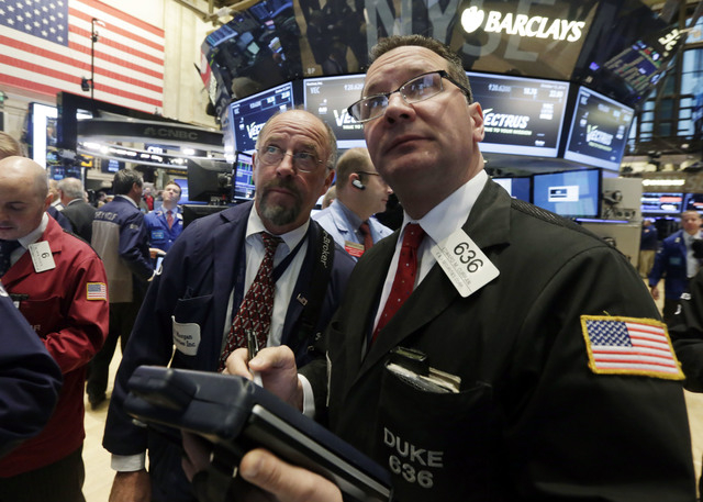 Traders Frederick Reimer, left, and Edward Curran work on the floor of the New York Stock Exchange, Monday, Oct. 13, 2014. U.S. stocks waffled between small gains and losses after the market clock ...