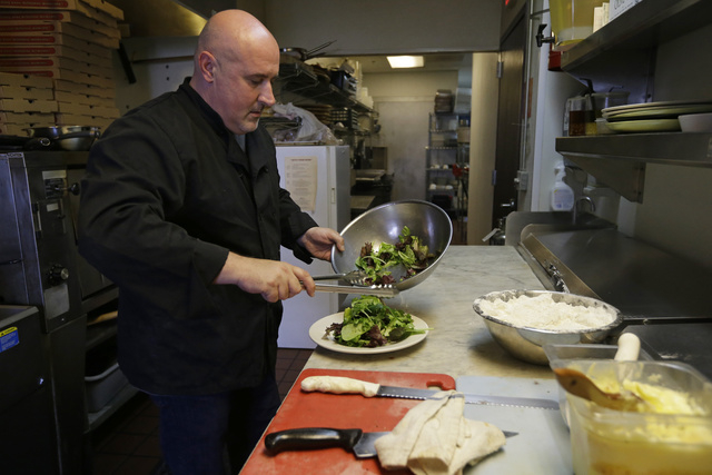 Chef Michele Massimo prepares a salad in the kitchen of his restaurant Botto Bistro Wednesday, Oct. 1, 2014, in Richmond, Calif. For years, many small businesses have complained that Yelp is extor ...