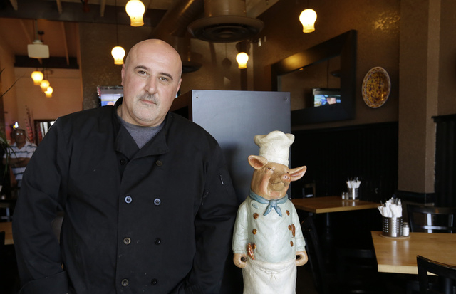 Chef Michele Massimo poses in the dining room of his restaurant Botto Bistro Wednesday, Oct. 1, 2014, in Richmond, Calif. For years, many small businesses have complained that Yelp is extorting th ...