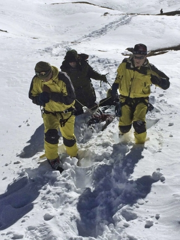 In this photo released by the Nepalese Army, rescue team members carry a victim of an avalanche before they airlift the body from Thorong La pass area, in Nepal, Thursday, Oct. 16, 2014. Search te ...