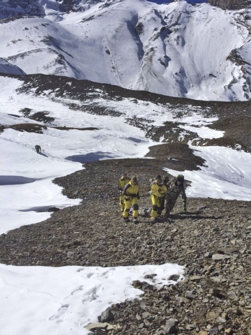 In this photo provided by the Nepalese Army, rescue team members carry a victim of an avalanche before they airlift the body from Thorong La pass area in Nepal, Thursday, Oct. 16, 2014. Search tea ...
