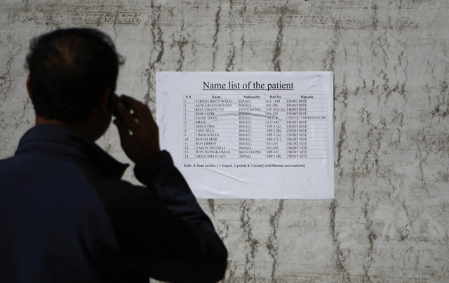 Nepalese trekking agent stands in front a patients list at the Army hospital in Katmandu, Nepal, Thursday, Oct. 16, 2014. At least 14 foreign trekkers have been rescued so far, including two from  ...