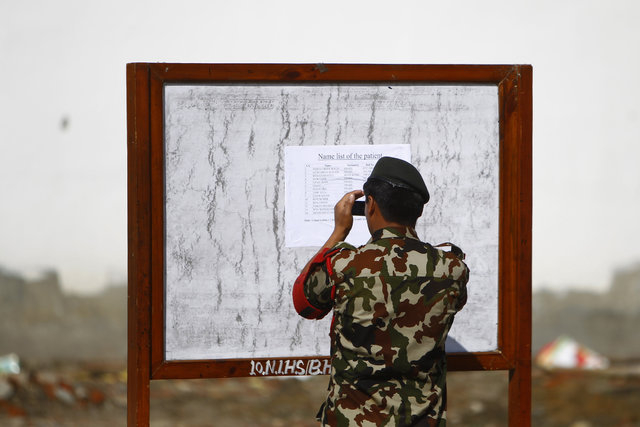 A Nepalese army soldier takes a photo of a patients list at the Army hospital in Katmandu, Nepal, Thursday, Oct. 16, 2014. At least 14 foreign trekkers have been rescued so far, including two from ...
