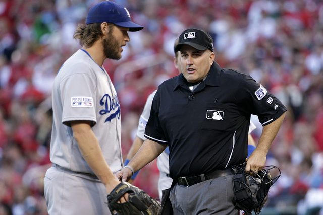 In this Oct. 7, 2014, file photo, Los Angeles Dodgers starting pitcher Clayton Kershaw, left, talks with home plate umpire Eric Cooper during Game 4 of baseball's NL Division Series against the St ...
