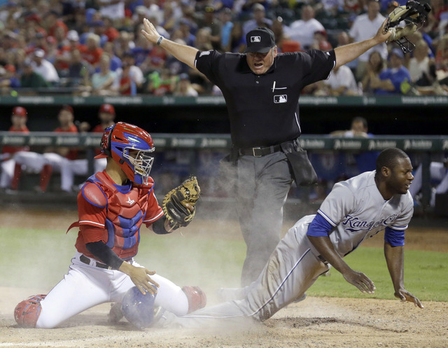 In this Aug. 23, 2014, file photo, home plate umpire Hunter Wendelstedt, center, calls Kansas City Royals' Lorenzo Cain, right, safe at home after Cain scored against Texas Rangers catcher Robinso ...