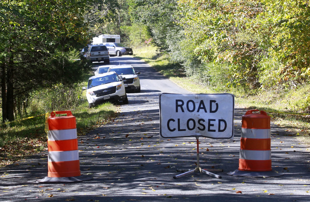 A road closed sign blocks traffic as authorities search a rural area where human remains were discovered in Albermarle County, Va., Sunday, Oct. 19, 2014. Investigators also interviewed residents  ...