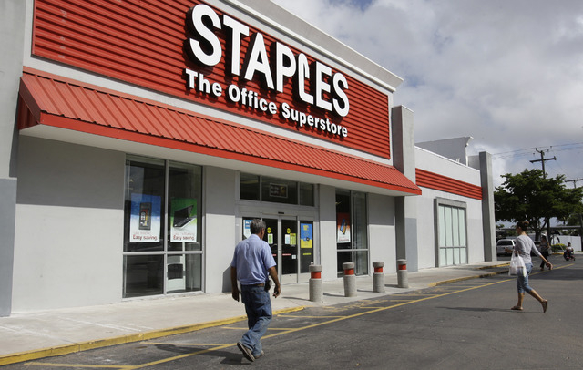 FILE - In this Tuesday, Nov. 15, 2011, file photo, customers enter Staples office supply store in Miami. Staples on Tuesday, Oct. 21, 2014 said it is looking into a potential credit card data brea ...