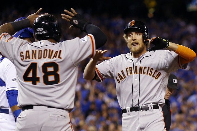 San Francisco Giants' Hunter Pence is congratulated by Pablo Sandoval after Pence hit a two-run home run during the first inning of Game 1 of baseball's World Series against the Kansas City Royals ...
