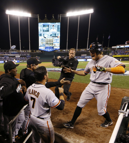 San Francisco Giants Hunter Pence, right, is congratulated by his teammates after hitting a two-run home run during the first inning of Game 1 of baseball's World Series Tuesday, Oct. 21, 2014, in ...