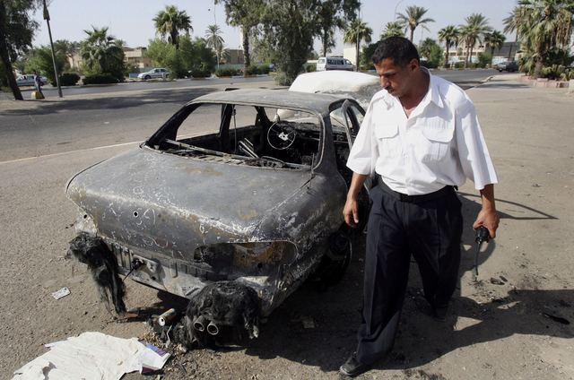 In this Sept. 25, 2007 file photo, an Iraqi traffic policeman inspects a car destroyed by a Blackwater security detail in al-Nisoor Square in Baghdad, Iraq. A federal jury reached a verdict Wednes ...