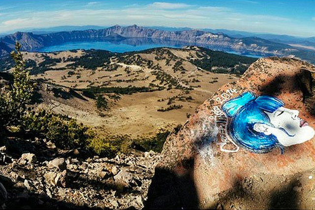 This undated photo taken from an Instagram posting shows an overlook of Crater Lake in Oregon with a rock painting. The National Park Service is investigating paintings and drawings of eerie faces ...