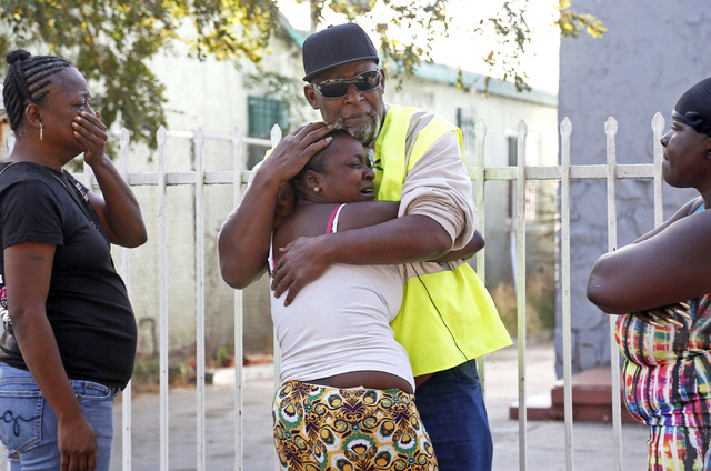 Danisha Mitchell is hugged by a relative at the scene of the accident Thursday, Oct. 23, 2014, a day after her 7-year-old son Jamarion Thomas was killed in when his motorized bicycle collided with ...