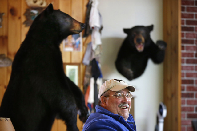 In this Friday, Sept. 19, 2014 photo, Jim Vohland, the mayor of Peppertown, Ind., talks with fellow out-of-state bear hunters at a hunting lodge in Wilton, Maine. Many hunters say the ban on bear- ...
