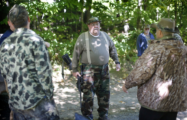 In this photo made Friday, Sept. 19, 2014, Jim Vohland, the mayor of Peppertown, Ind., talks with fellow out-of-state bear hunters before heading into the woods in Wilton, Maine. A Maine ballot qu ...