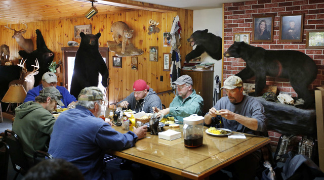 In this Friday, Sept. 19, 2014 photo, out-of-state bear hunters eat a meal at the Stony Brook Outfitters lodge in Wilton, Maine. Maine voters will decide on a proposal to ban the use of bait, dogs ...