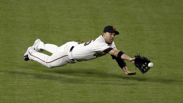 San Francisco Giants' Travis Ishikawa can't catch a double hit by Kansas City Royals' Omar Infante during the fifth inning of Game 5 of baseball's World Series Sunday, Oct. 26, 2014, in San Franci ...