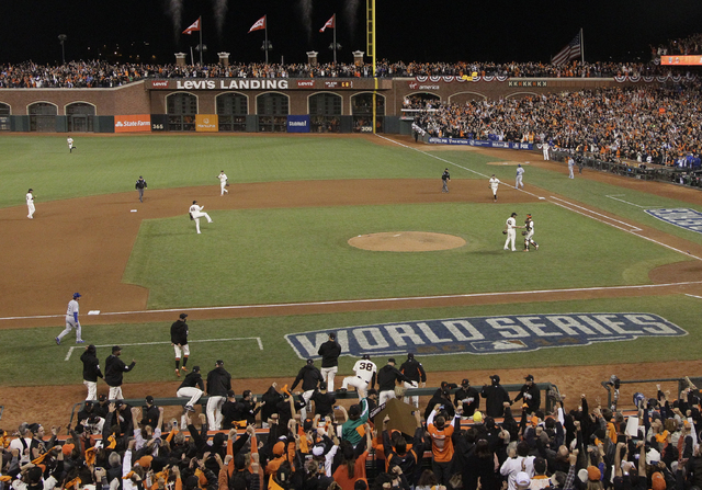 San Francisco Giants celebrate as catcher Buster Posey shakes hands with pitcher Madison Bumgarner after defeating the Kansas City Royals 5-0 in Game 5 of baseball's World Series Sunday, Oct. 26,  ...