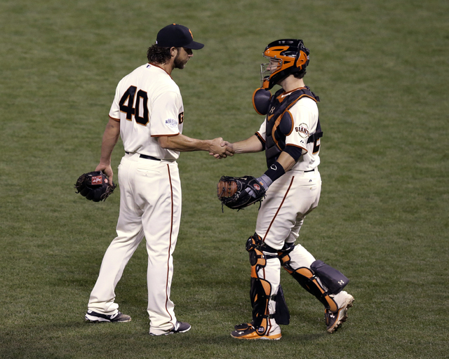 San Francisco Giants catcher Buster Posey shakes hands with pitcher Madison Bumgarner after defeating the Kansas City Royals 5-0 in Game 5 of baseball's World Series Sunday, Oct. 26, 2014, in San  ...