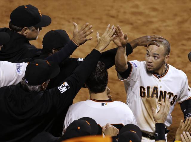 San Francisco Giants Juan Perez, right, is congratulated after hitting two-run RBI double during the eighth inning of Game 5 of baseball's World Series Sunday, Oct. 26, 2014, in San Francisco. The ...