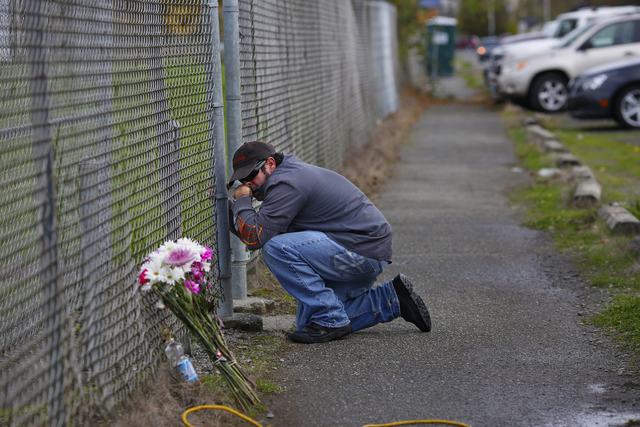 Dale Zachry, who graduated from Marysville-Pilchuck High School in 1986, stopped for a prayer at the fence surrounding the school grounds in Marysville, Wash., Saturday, Oct. 25, 2014. (AP Photo/T ...