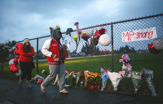 A memorial grows Saturday Oct. 25, 2014 at the entrance to Marysville Pilchuck High School the day after a shooting in the school cafeteria left two dead and four wounded. The shooter was among th ...