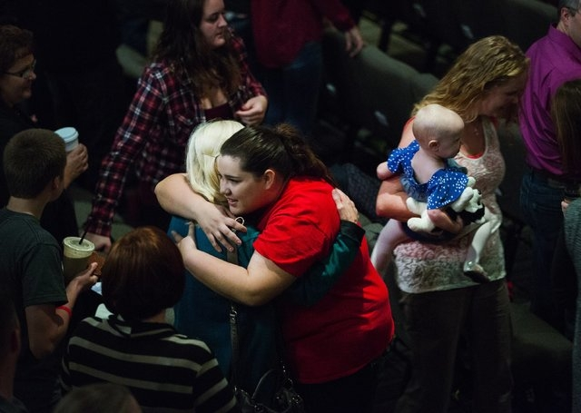 A girl wearing a Marysville-Pilchuck shirt, in red, hugs another woman as people greet each other during a morning service at The Grove Church in Marysville, Wash., two days after the Marysville-P ...