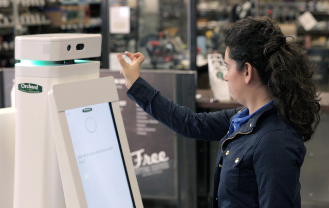 In this undated image provided by Lowe's, a woman holds a nail up to be scanned by an OSHbot robot. The robots are equipped with 3D cameras so they can scan and identify items. And customers can r ...